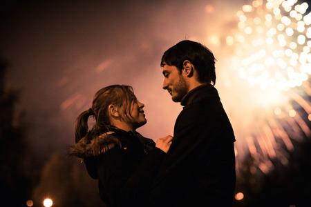 巨大な花火の前でキス カップルのシルエットです。穀物でフィルターされたイメージ