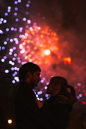 A silhouette of a kissing couple in front of a huge fireworks display. Filtered image with grain