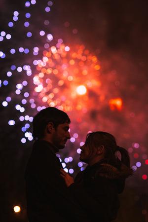 Een silhouet van een kussen paar in de voorkant van een groot vuurwerk. Gefilterde afbeelding met graan
