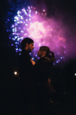 fireworks display: A silhouette of a kissing couple in front of a huge fireworks display. Filtered image with grain