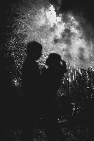 romantically: A silhouette of a kissing couple in front of a huge fireworks display. Filtered black and white image with grain Stock Photo