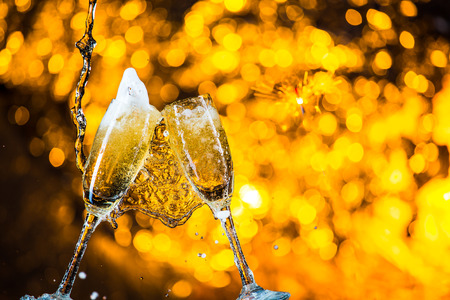 a pair of champagne flutes with golden bubbles make cheers on golden light background with space for  text Stock Photo
