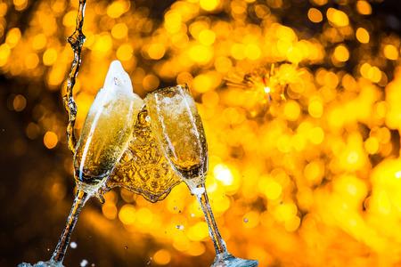 sektglas: ein Paar Champagner Fl�ten mit goldenen Blasen machen cheers auf goldenen hellen Hintergrund mit Platz f�r Text Lizenzfreie Bilder