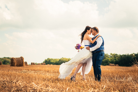 Bride and groom near hay on  a rural field