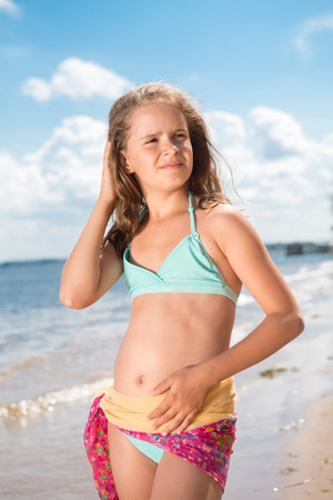 pink posing: Portrait of merry little girl  posing at camera on beach