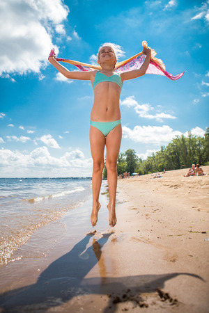 Little girl jumping high in water  of a sea