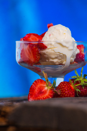 ice cream glass: Strawberry ice  cream with wooden and blue background Stock Photo