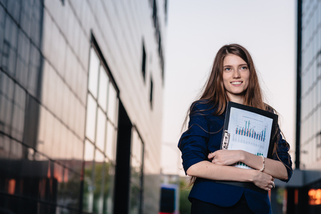 to the secretary: Successful smiling businessman, standing against the backdrop of buildings  holding  folder with sales charts. City business woman working. Stock Photo