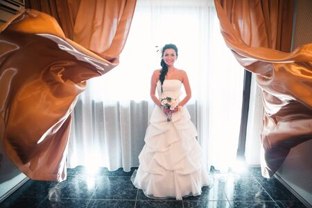 beautiful young happy   bride standing near the window