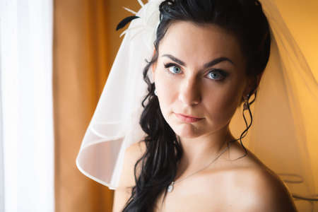 beautiful young bride  costs about stylish window