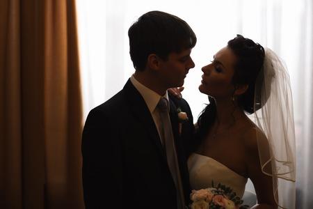honeymoon suite: beautiful young  couple standing near the window