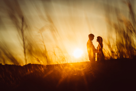 Romantic silhouette  couple standing and kissing on background summer meadow sunset