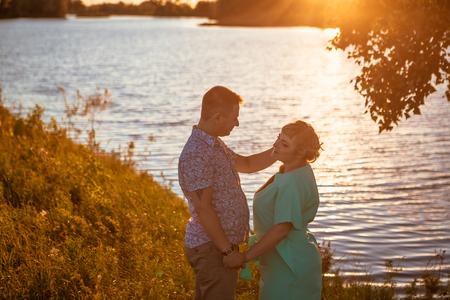 lake sunset: Romantic couple standing  and kissing on background summer lake sunset Stock Photo
