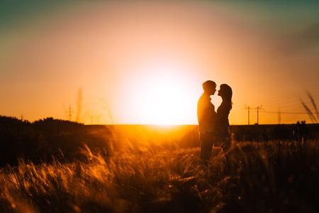 ロマンチックなシルエット カップル立っていると背景夏草原夕日にキス