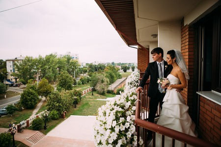 honeymoon suite: beautiful young  couple stand on the balcony
