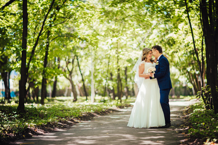 summer dress: Happy couple  bride and groom embracing they stand in a forest full length