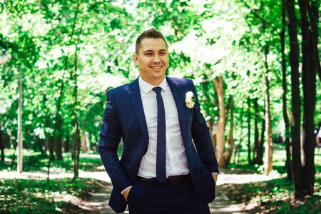 background summer: gorgeous stylish elegant happy groom standing in light on a background of beautiful sunny trees in a forest