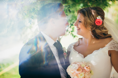 woman in dress: Happy couple  bride and groom embracing they stand on background nature close-up