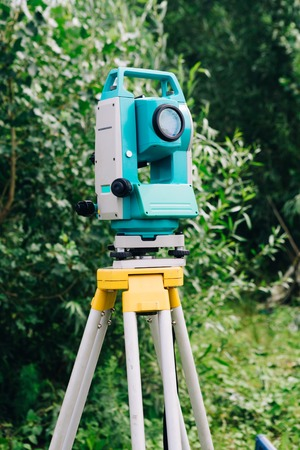 blue surveying  equipment total station on a background of lake and forest