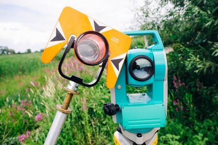 exact position: orange theodolite prism and blue surveying equipment total station on a background of lake Stock Photo