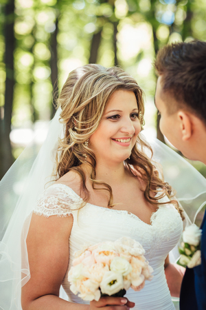summer dress: Happy couple bride and groom embracing they stand  in a forest