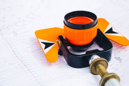 exact position: orange theodolite prism  lies on a background of geodetic maps of the area