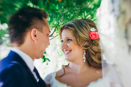 summer dress: Happy couple  bride and groom embracing they stand on background stone wall close-up