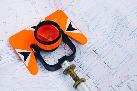 Oranje theodoliet prisma ligt op een achtergrond van geodetische kaarten van het gebied