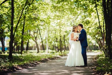 フォレストのフルの長さに立つ幸せなカップルの花嫁と花婿を採用 写真素材