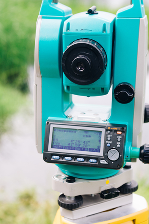 mensuration: blue surveying  equipment total station on a background of lake and forest