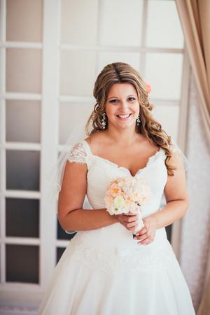 blond hair: elegance cute  bride is posing on the  background room