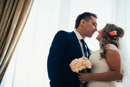 two men: Bride and groom posing in  a hotel room on background windows