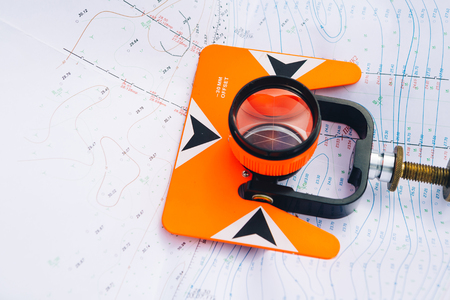 construction level: orange theodolite prism  lies on a background of geodetic maps of the area