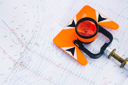 tacheometer: orange theodolite prism  lies on a background of geodetic maps of the area
