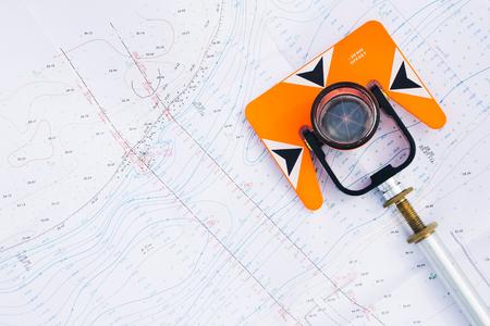 Oranje theodoliet prisma ligt op een achtergrond van geodetische kaarten van het gebied Stockfoto - 49215304