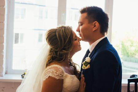 parejas romanticas: Bride and groom posing  in a hotel room on background windows