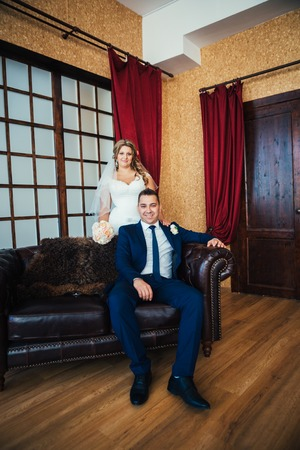 stylish man: Bride and groom posing  in a hotel room
