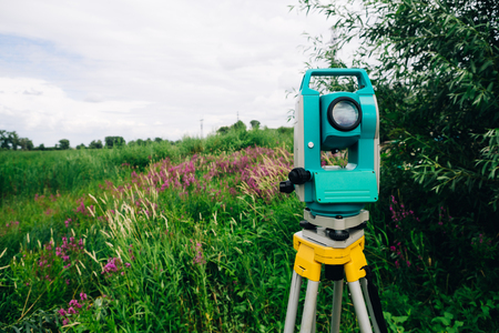 mensuration: blue surveying  equipment total station on a background of meadow