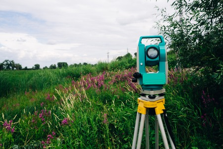 exact position: blue surveying  equipment total station on a background of meadow
