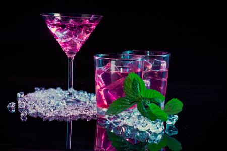 martini: wine glass and two glasses with pink martinis, fine fragments of ice, fresh mint on  a dark mirror background