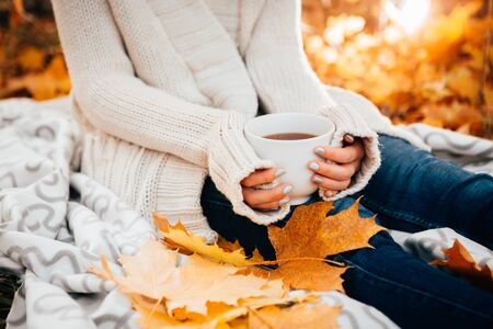 relajado: Mujer joven en un suéter y pantalones vaqueros relajante té de la bebida en el fondo de otoño