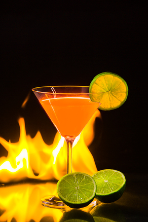 carroty: colorful orange cocktail  in nice carroty color to front of a black background and fire