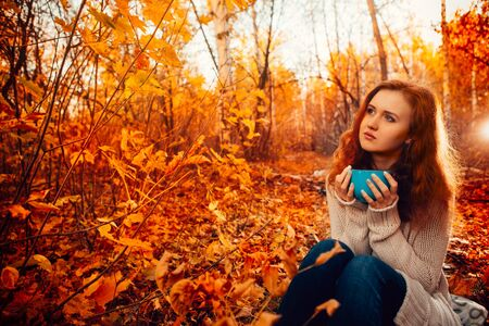leaning: Young woman in a sweater and jeans relaxing drink tea on autumn  background