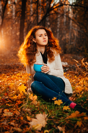 Young woman in a sweater and jeans relaxing drink tea on autumn  background photo