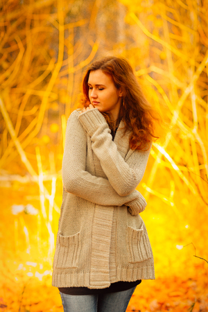 Young woman  in a sweater and jeans stand on autumn background photo