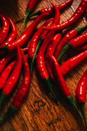 red chili pepper: red and green chili peppers  close up on wooden background