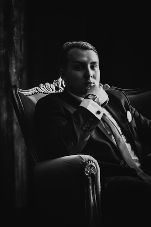 black and white photography: Black white  photography portrait of man in black classic  suit on a dark background.