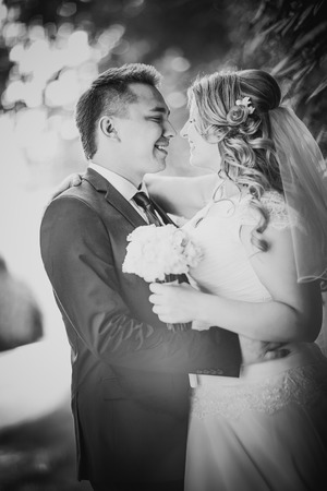 black and white photography: Black white  photography happy couple  bride and groom embracing they stand on background nature close-up