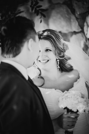 black and white photography: Black white photography happy couple  bride and groom embracing they stand on background stone wall close-up Stock Photo