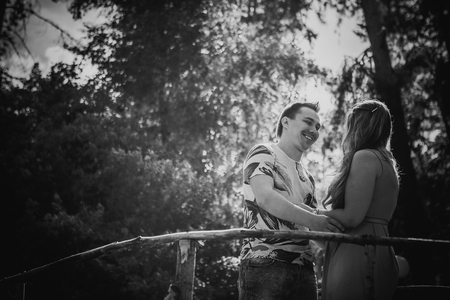 black and white photography: Black white photography  romantic young couple kissing  and stand to bridge on background